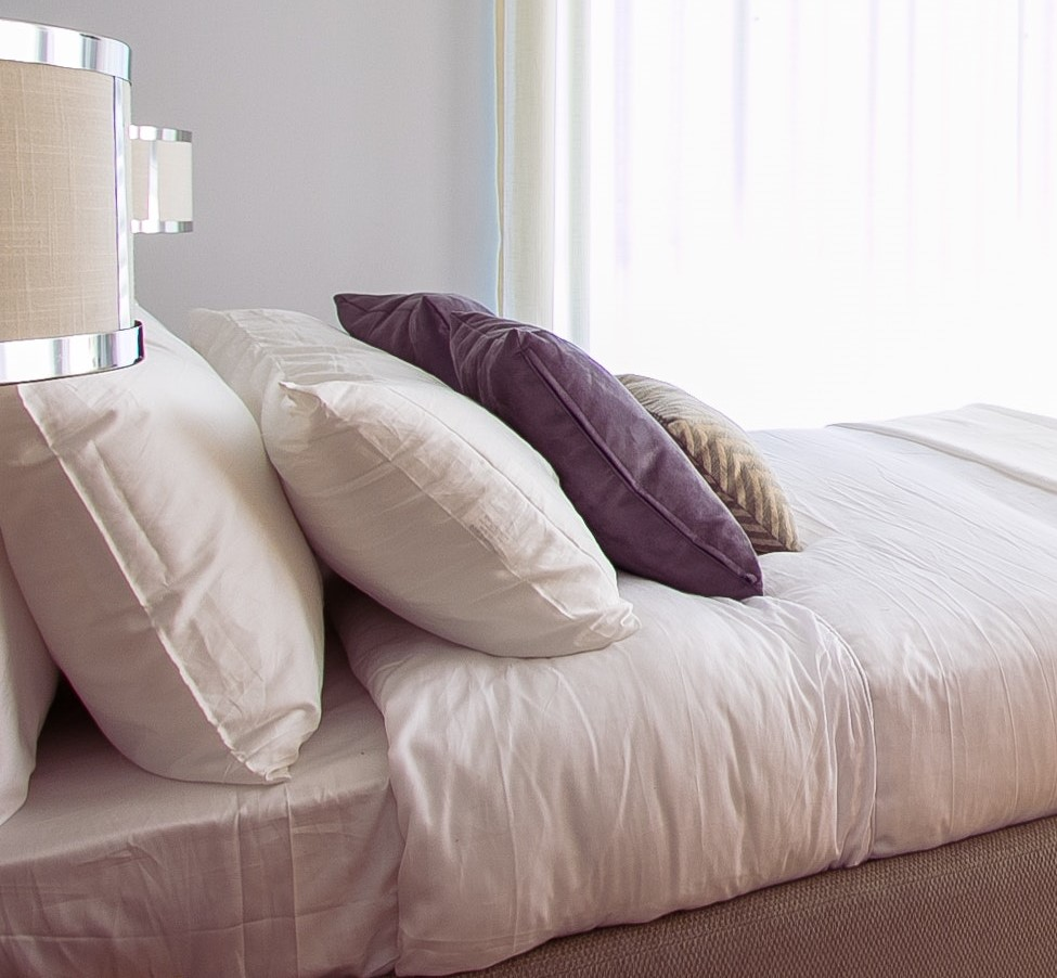 Which pillow is best? Four pillows on mattress.